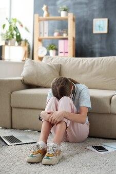 Nieszczęśliwa nastolatka trzymająca twarz między kolanami, siedząca na podłodze przy kanapie i wyrażająca smutek z powodu domowej kwarantanny