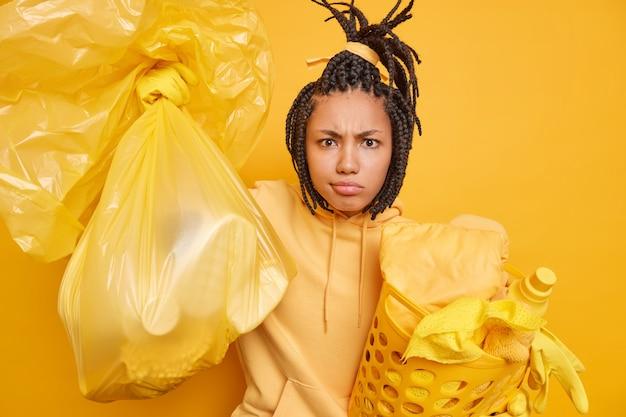 Nieszczęśliwa niezadowolona etniczna kobieta z dredami nosi bluzę z torbą na śmieci