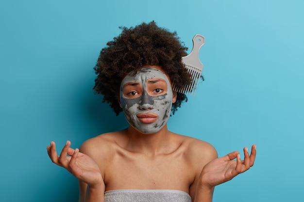 Nieszczęśliwa niezdecydowana afroamerykańska kobieta z grzebieniem wetkniętym w kędzierzawe naturalne włosy, ze zdumieniem rozkłada ręce na boki, nie umie czesać, nosi kosmetyczną maskę na twarz, ręcznik kąpielowy wokół ciała