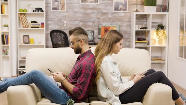 Nieszczęśliwa para siedzi plecami do siebie na kanapie. para pożera się nawzajem za pomocą telefonów.