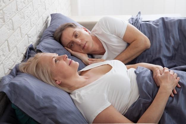 Nieszczęśliwa para w średnim wieku w sypialni w domu.