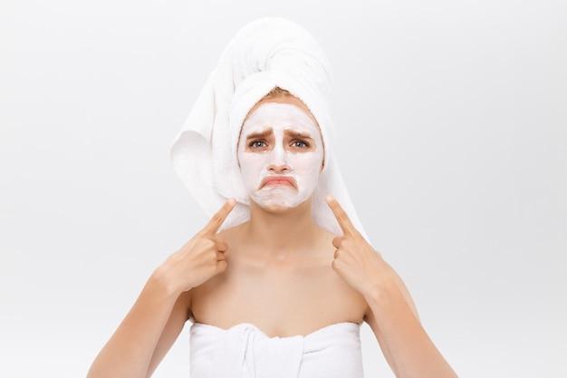 Nieszczęśliwa piękna młoda kobieta z białą glinianą maską robi terapia przeciwtrądzikowa, jest ubranym białego ręcznika na włosy, pozuje przeciw białej studio ścianie.