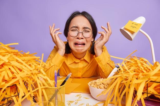 Nieszczęśliwa przygnębiona azjatycka uczennica pracuje do późna, przygotowuje się do testu, czy zadanie domowe ma dużo zadań do wykonania, płacze z rozpaczy, siedzi przy biurku sama, czuje się przepracowana, płacze z rozpaczy