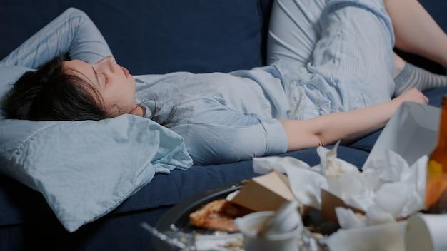 Nieszczęśliwa przygnębiona kobieta leżąca na kanapie wyglądająca na zagubioną przy brudnym stole