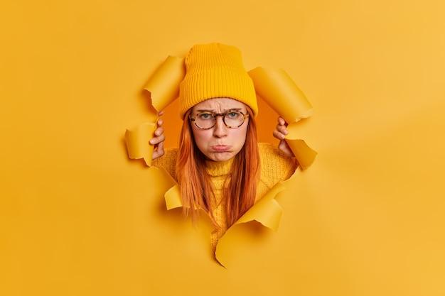 Nieszczęśliwa, rozczarowana młoda kobieta zaciska usta i wygląda na urażoną, przebijając się przez papierową dziurkę