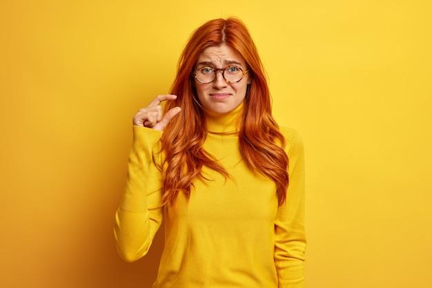 Nieszczęśliwa ruda kobieta robi mały gest, demonstrując coś malutkiego ubranego w swobodny sweter.