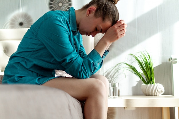 Nieszczęśliwa, samotna, przygnębiona kobieta czuje się samotna, bezbronna, zmęczona. cierpi na ból głowy, migrenę i ból