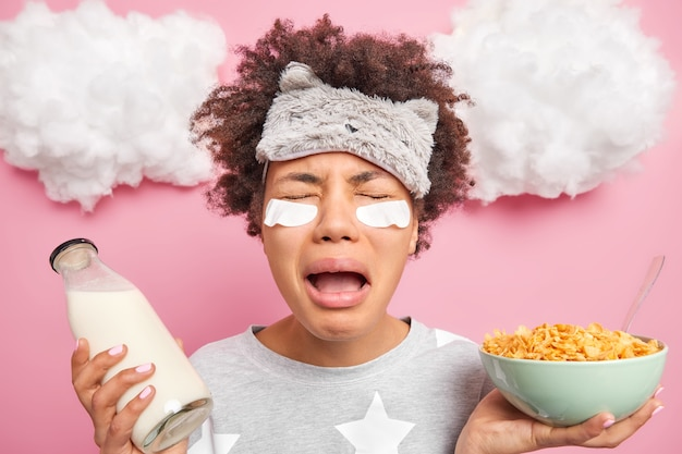 Nieszczęśliwa sfrustrowana afroamerykanka płacze z rozpaczy budzi się w łóżku nie chce iść do łóżka trzyma miskę płatków kukurydzianych i mleka idzie na śniadanie nosi piżamę