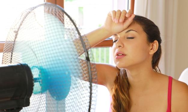 Nieszczęśliwa studentka w domu w upalny letni dzień przed pracującym wentylatorem cierpiącym na letnie upały.