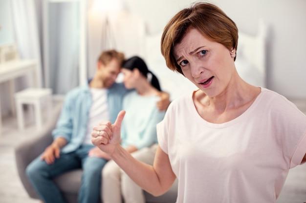 Nieszczęśliwa teściowa. beztroska starsza kobieta patrzy na ciebie i martwi się o swojego syna