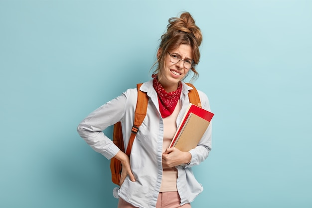 Nieszczęśliwa uczennica lub studentka nosi ciężki plecak z książkami, cierpi na bóle pleców, trzyma notatnik, dotyka talii, odizolowana na niebieskiej ścianie. sfrustrowany nastolatek ma problemy ze zdrowiem