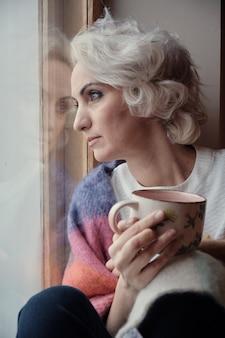 Nieszczęśliwa zamyślona dojrzała kobieta pije herbatę i wygląda przez okno, blokada i koncepcja izolacji, selektywna ostrość