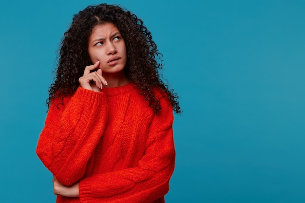 Nieszczęśliwa zamyślona młoda kobieta, patrząc w prawy górny róg, trzymając palec w pobliżu policzka