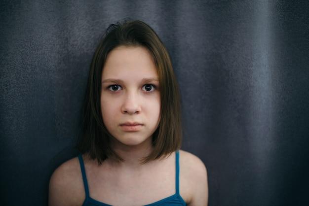 Nieszczęśliwa, zasmucona i przygnębiona dziewczynka z wyrazistymi oczami z bliska na zasłonie