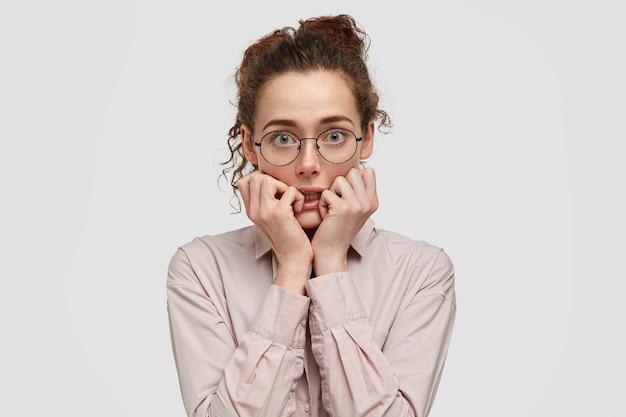 Nieszczęśliwa zdenerwowana młoda kobieta o zmartwionym wyrazie, obgryza paznokcie, patrzy wprost z niepokojem, nosi okulary, ubrana w modne ciuchy, stoi pod białą ścianą.
