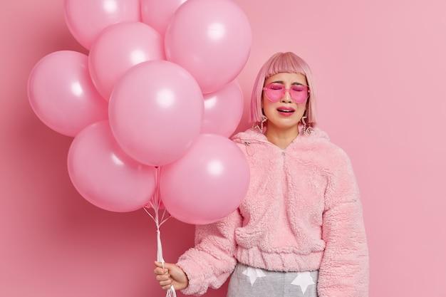 Nieszczęśliwa zdesperowana kobieta płacze, gdy nikt nie przychodzi na jej przyjęcie, czuje się samotny i zdenerwowany trzyma pęk nadmuchanych balonów