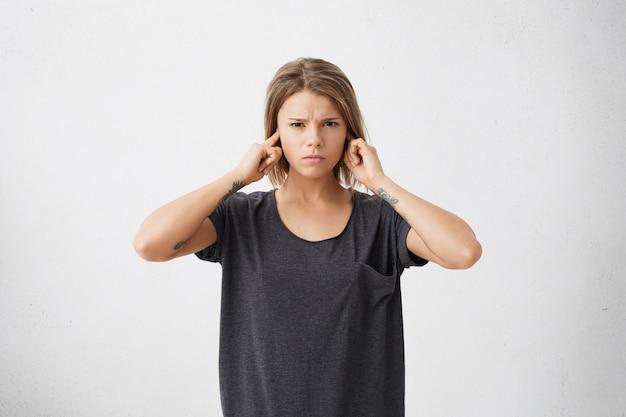 Nieszczęśliwa zestresowana nastolatka zatykająca uszy palcami nie chce słyszeć irytującego hałasu lub ignorowania stresującej i nieprzyjemnej sytuacji lub konfliktu.