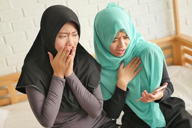 Nieszczęśliwe islamskie kobiety korzystające ze smartfona, sfrustrowana azjatycka muzułmanka grająca na smartfonie, islamskie kobiety muzułmańskie korzystające, czytające z wolnym połączeniem internetowym przez smartfon, mały mobilny tablet komputerowy