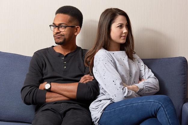 Nieszczęśliwe pary różnych ras siedzą wygodnie, nie rozmawiają ze sobą po kłótni lub sporze, trzymają ręce skrzyżowane, nieporozumienia i nieporozumienia.