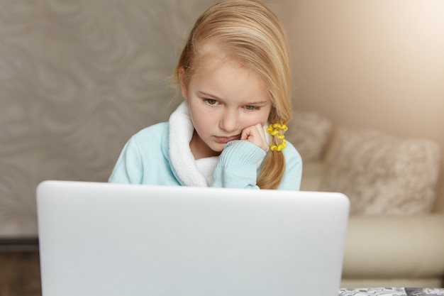 Nieszczęśliwe słodkie dziecko płci żeńskiej z niechlujnymi włosami, trzymając rękę na brodzie podczas pracy domowej