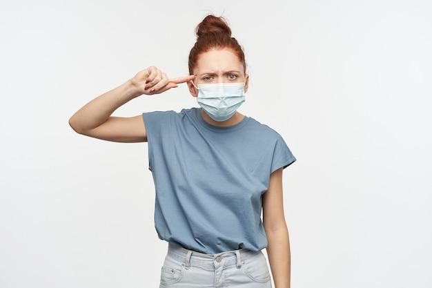 Nieszczęśliwie wyglądająca kobieta z rudymi włosami zebranymi w kok. noszenie ochronnej maski na twarz. trzymaj palec na skroni odizolowanej od białej ściany
