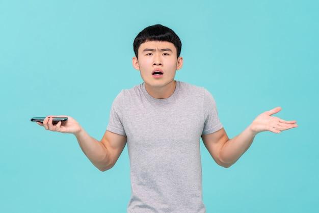 Nieszczęśliwy azjatycki człowiek mający kłopoty ze swoim smartfonem