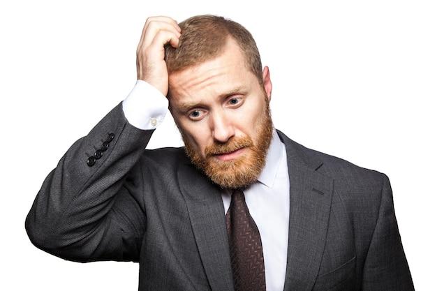 Nieszczęśliwy biznesmen smutny myśli z ręką na głowie. na białym tle, patrząc w kamerę...