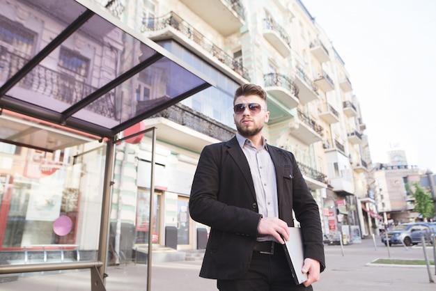 Nieszczęśliwy biznesmen stojący z laptopem w ręku na tle architektury.