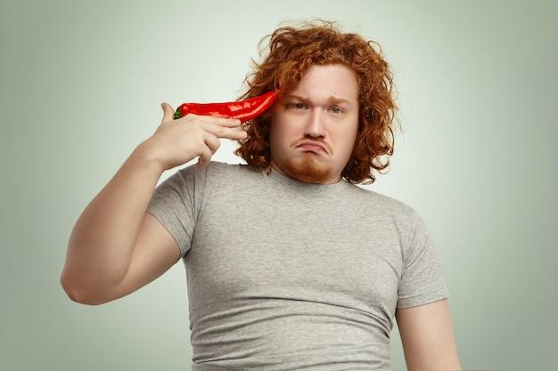 Nieszczęśliwy, brodaty, młody, otyły mężczyzna z nadwagą czuje się nieszczęśliwy i sfrustrowany pierwszego dnia diety warzywnej, wykrzywiając usta, trzymając czerwoną paprykę w świątyni, jakby próbował się zastrzelić