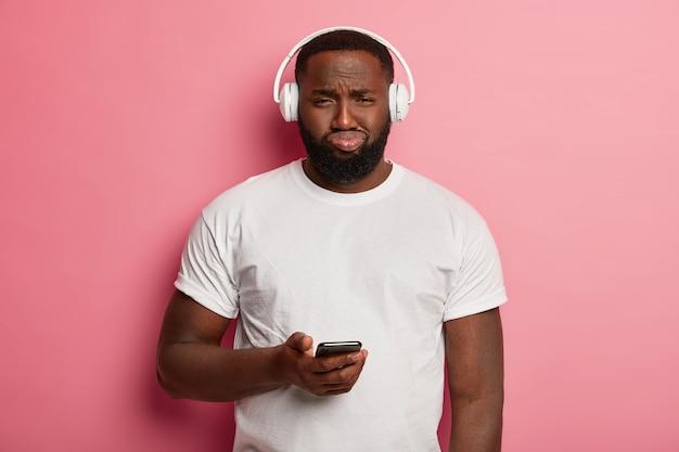 Nieszczęśliwy czarny nieogolony mężczyzna słucha muzyki w słuchawkach, ma niezadowolony wyraz twarzy, trzyma telefon komórkowy, ubrany niedbale, zdenerwowany, że nie może pobrać piosenki z listy odtwarzania