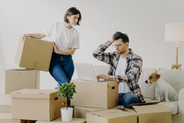 Nieszczęśliwy człowiek w okularach siedzi przed nowoczesnym laptopem, pracuje zdalnie w domu
