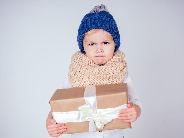 Nieszczęśliwy mały uśmiechnięty blond kręcone fryzury chłopiec w dzianym niebieskim kapeluszu z świątecznym pudełkiem z kokardą na białym tle w studio. prezent noworoczny w rękach smutnego dziecka płci męskiej