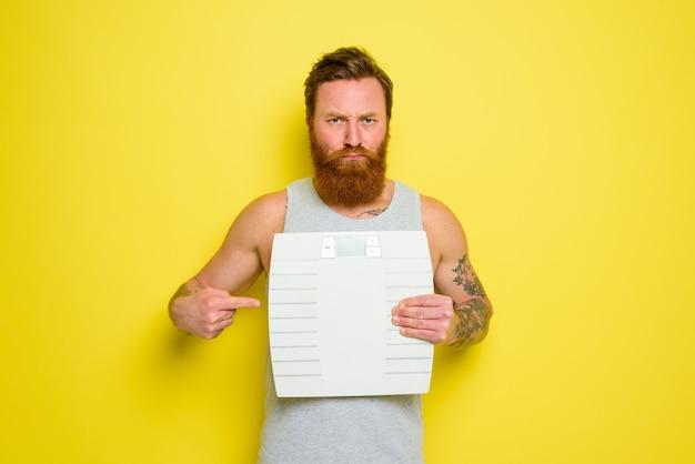 Nieszczęśliwy mężczyzna z brodą i tatuażami trzyma równowagę elektroniczną
