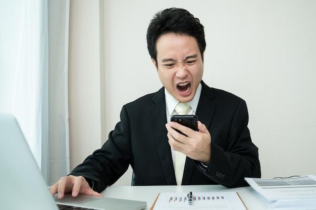 Nieszczęśliwy młody biznesmen z azji czuje się bardzo zdenerwowany i zrozpaczony z powodu niestabilnej sytuacji ekonomicznej i niepowodzenia w biznesie. przygnębiony - zestresowany biznesmen mający problem. stresujący azjatycki człowiek pracujący.