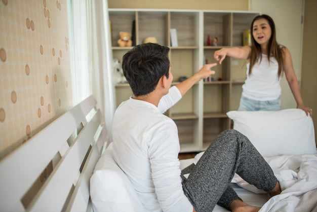Nieszczęśliwy młody człowiek ma argument z jego dziewczyną w łóżkowym pokoju