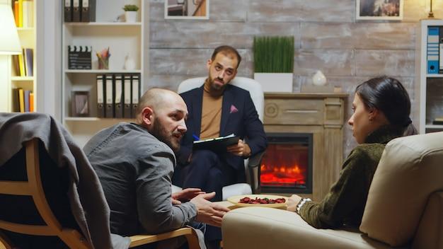 Nieszczęśliwy młody mężczyzna i żona rozmawiają o swoim związku. specjalista od małżeństw.
