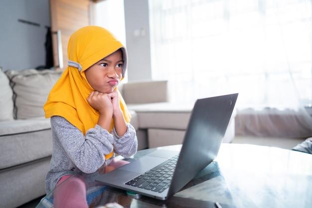 Nieszczęśliwy młody muzułmanin podczas nauki w domu przy użyciu laptopa