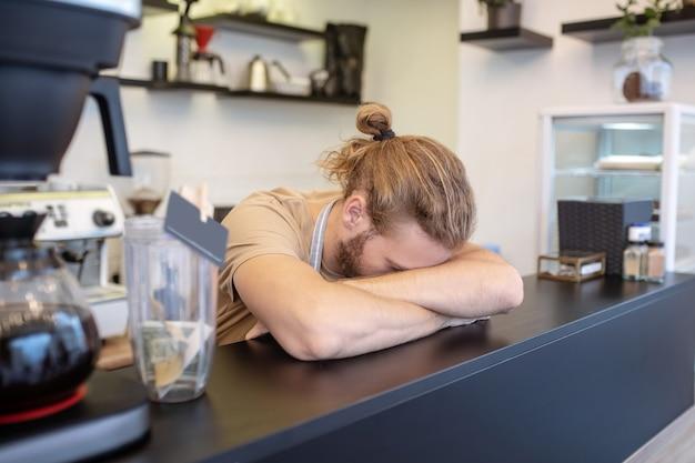 Nieszczęśliwy moment. długowłosy mężczyzna z głową na rękach, chowając twarz za ladą barową w kawiarni