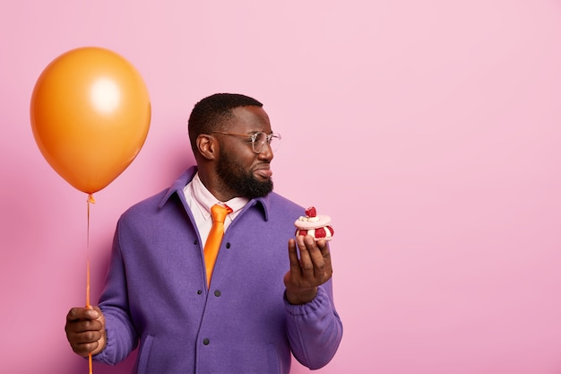 Nieszczęśliwy murzyn z brodą zmęczony przygotowaniami do przyjęcia, trzyma balon i babeczkę, patrzy z niezadowoleniem po prawej stronie, smutni goście nie przychodzą na urodziny, nosi formalną białą koszulę