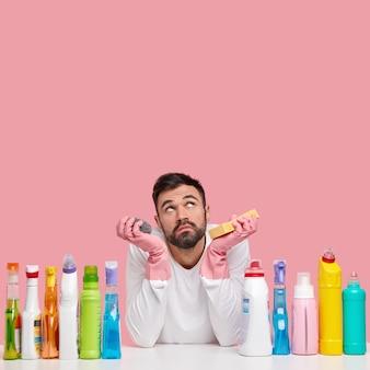Nieszczęśliwy, nieogolony mężczyzna ze smutną miną skupiony w górze, zastanawia się, który pokój najpierw wyczyścić, używa różnych detergentów