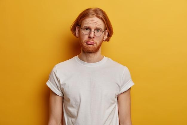 Nieszczęśliwy ponury hipster z rudymi włosami, gęstą brodą i dolną wargą w torebce
