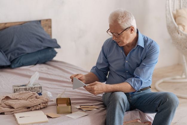 Nieszczęśliwy, przygnębiony starszy mężczyzna trzymający kopertę i patrząc na nią, czytając swoje stare listy