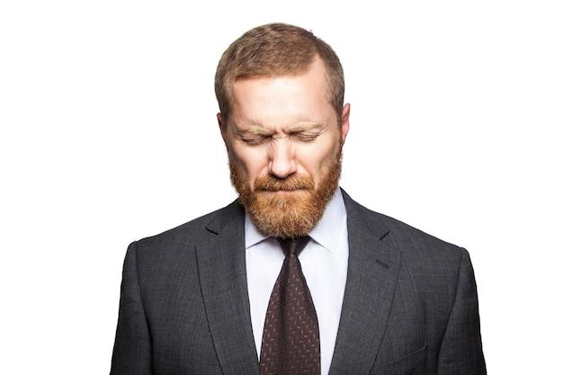Nieszczęśliwy smutny biznesmen z zamkniętymi oczami. na białym tle, patrząc w kamerę...