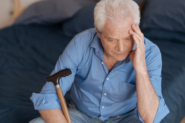 Nieszczęśliwy, smutny starszy mężczyzna siedzi na łóżku i dotyka głowy, myśląc o swojej przeszłości