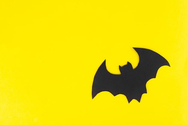 Nietoperz z czarnego papieru na żółtym tle tło widok z góry halloween