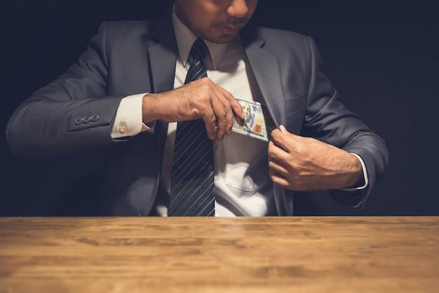 Nieuczciwy biznesmen wkładający pieniądze, dolary amerykańskie, do kieszeni swojego garnituru w ciemności