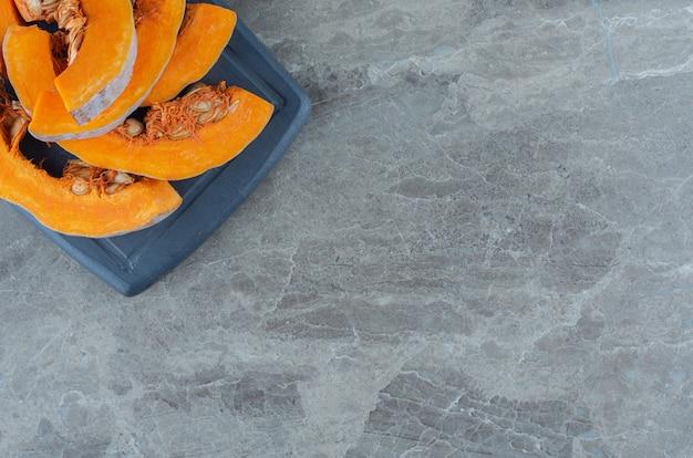 Nieugotowana dynia na desce, na marmurowym stole.