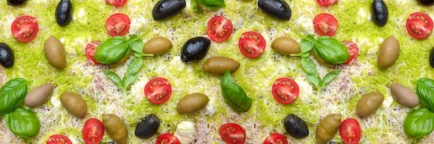 Nieugotowana pizza, tło. zbliżenie pizzy, widok z góry. surowa pizza z pomidorkami koktajlowymi, kolorowymi serami i oliwkami. transparent żywności.