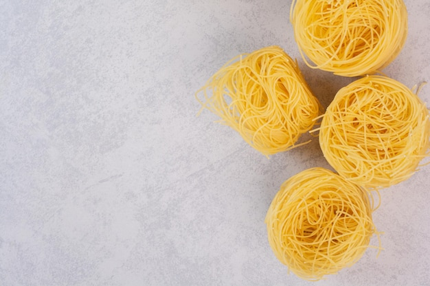 Nieugotowane spaghetti gniazd na marmurowym stole.