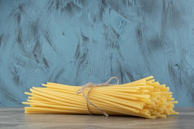 Nieugotowane spaghetti w rurce związane sznurkiem na marmurowej powierzchni